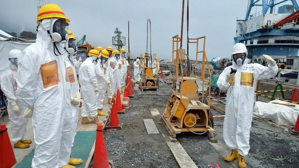 Local government officials and nuclear experts inspect a construction site on 6 August to prevent the seepage of contaminated water into the sea