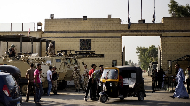 Troops stand guard outside one of the gates of the Tora prison where Mubarak is detained