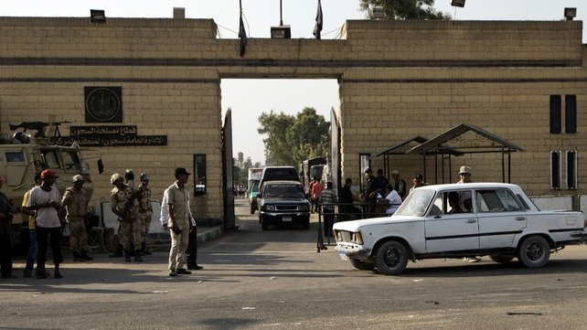 Security guards stand outside the entrance of Cairo's Tora prison