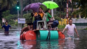 People use a makeshift raft to make their way through the streets of Manila following flooding in the Philippine capital