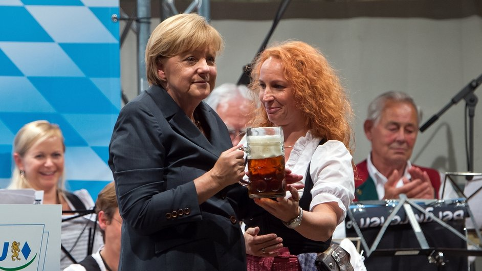 German chancellor Angela Merkel holds a beer after speaking in a beerfest tent while campaigning for upcoming federal elections