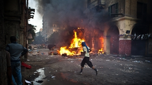 A supporter of the Muslim Brotherhood runs past a burning vehicle during clashes with security officers in Cairo
