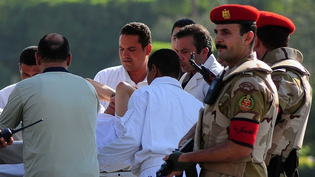 Egyptian security forces and medics wheel a stretcher transporting Hosni Mubarak from a military helicopter into an ambulance after his release from prison
