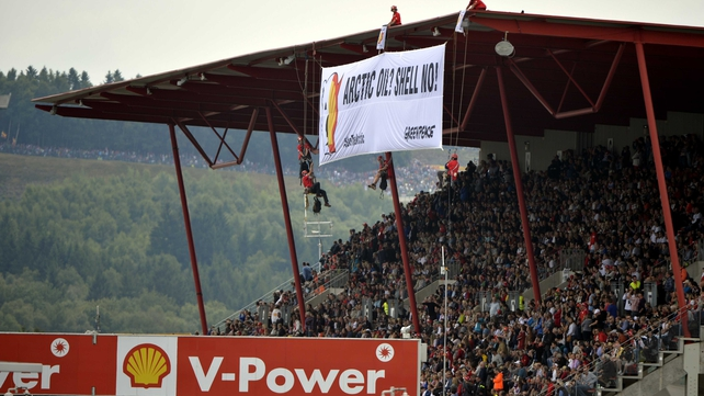 Anti-Shell protestors unfurl a banner at the Belgian Grand Prix