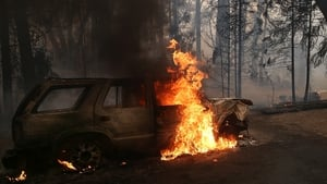 A car continues to burn after being consumed by the blaze