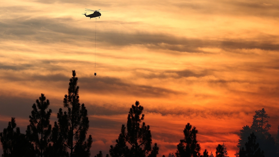 A helicopter prepares to drop water on the fire