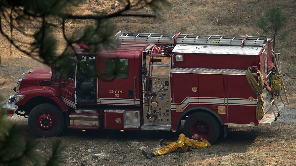 A fire fighter naps beside his truck in between shifts tackling the blaze