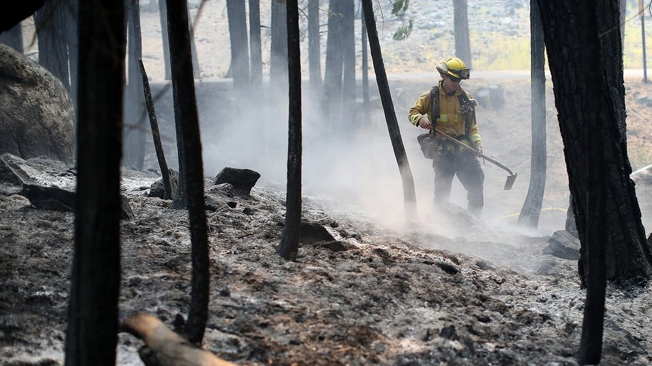 A fire fighter deals with any remaining 'hot spots' following the blaze