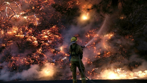 A fire fighter douses the flames as the fire rages on the edge of Yosemite National Park