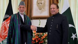 Afghan President Hamid Karzai and Pakistani Prime Minister Nawaz Sharif shake hands for photographers in Islamabad