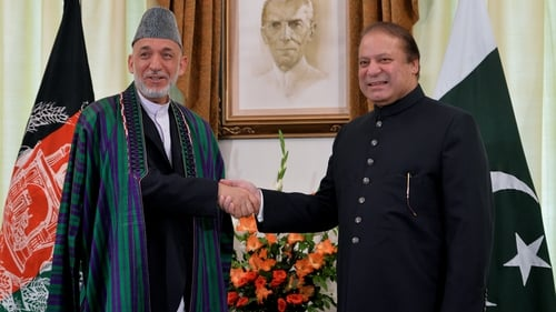 Afghan President Hamid Karzai and Pakistani Prime Minister Nawaz Sharif shake hands for photographers in Islamabad