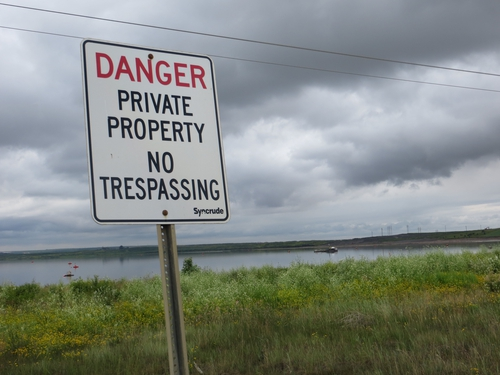 'No trespassing' sign at a tailings pond