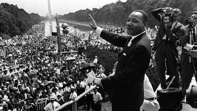 Civil rights leader Martin Luther King (C) waves to supporters 28 August 1963 on the Mall in Washington DC (Washington Monument in background) during the 'March on Washington'