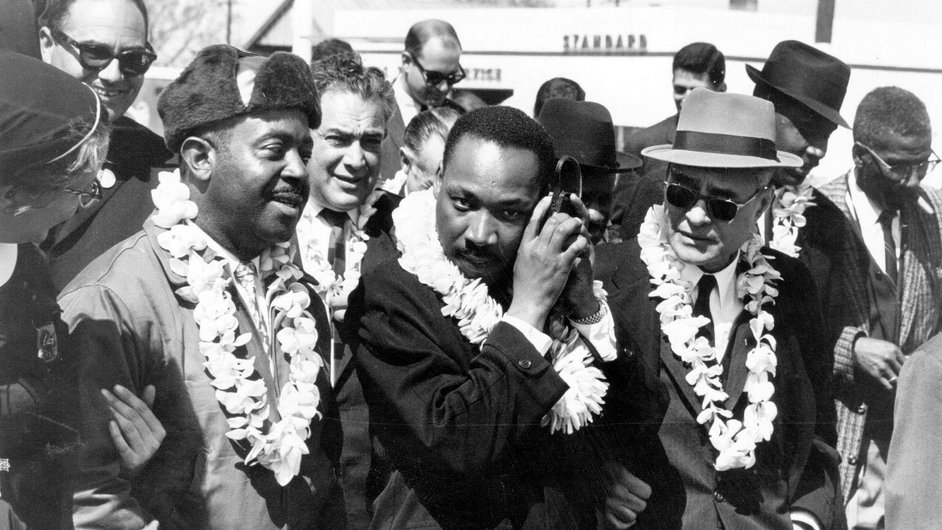 Martin Luther King listens to the radio while leading the Alabama Civil Rights march