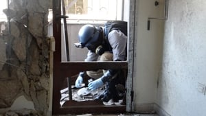 A UN worker inspects the site of an alleged chemical weapons attack in Syria