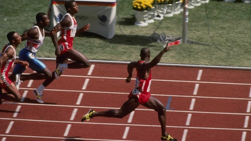 Ben Johnson (l) raises his arm as he finishes first in the 100m at the 1988 Olympics
