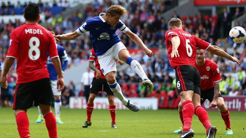 Nikica Jelavic of Everton heads the ball past Ben Turner of Cardiff