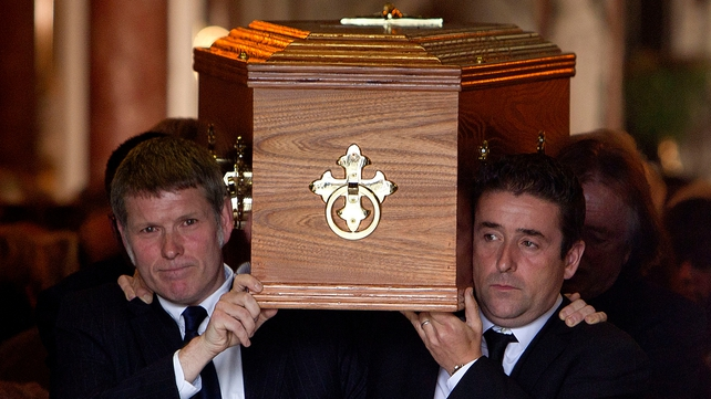 Michael (left) and Christopher Heaney carry their father's coffin