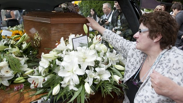 A mourner touches the coffin of Seamus Heaney after his funeral at the Sacred Heart Church