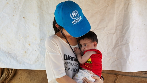 Eujin Byun, a UNHCR staff member, holds a young Syrian refugee in an informal settlement outside of Dalhamiyeh in the Bekaa Valley, Lebanon (Pic: UNHCR/S Baldwin)