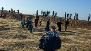 A Syrian boy carrying a heavy bag runs ahead as his family crosses the border into Jordan (Pic: UNHCR/O Laban-Mattei)