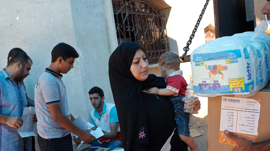 Syrian refugees wait in line to receive hygiene kits at a distribution centre in Zahle, Lebanon (Pic: UNHCR/S Baldwin)