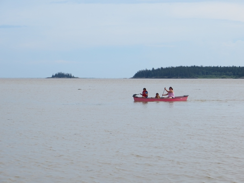 Children play in a canoe on Lake Athabasca