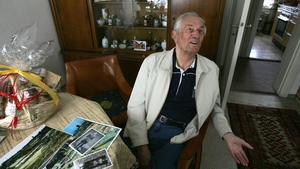 Rochus Misch sitting in his home in Berlin in 2005, with pictures of himself during the war