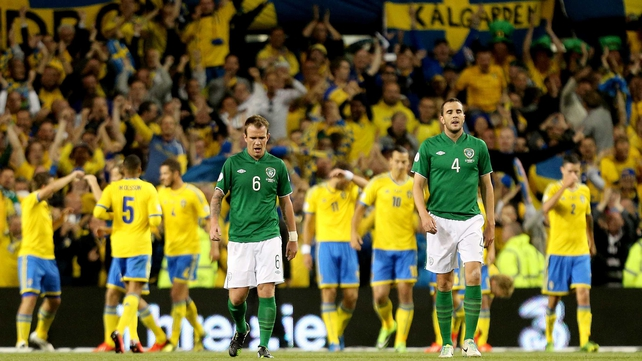 Glenn Whelan and John O'Shea dejected amongst a backdrop of Swedish celebration