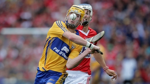 Clare's Colm Galvin clears the ball despite the attention of Luke O'Farrell