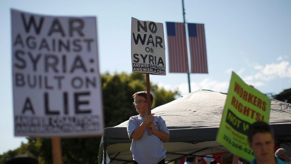 A boy holds a protest sign at a rally to urge Congress to vote against a limited military strike against the Syrian regime