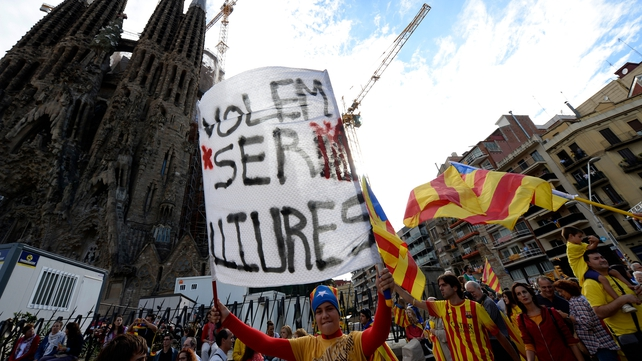 A Catalan holds a banner reading 'We want to be free' as he and thousands of Catalans gather to create a 400km human chain in front of the Sagrada Familia basilica in Barcelona