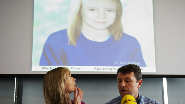 Kate and Gerry McCann sit beneath a projection of an artist's impression of how their daughter might look now