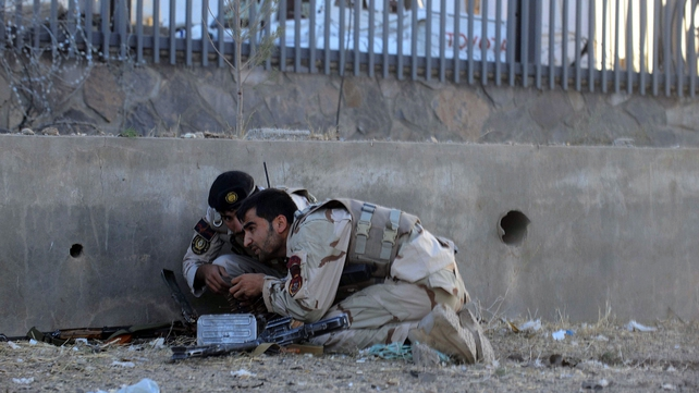Security forces take cover during the attack in Herat