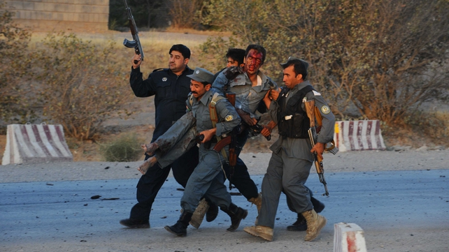 Police carry a wounded colleague to safety