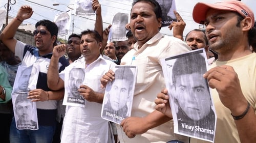 Pictures of the men involved in the gang rape are held by protesters