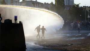 Turkish students run from water cannon and tear gas fired by police during a protest in Ankara
