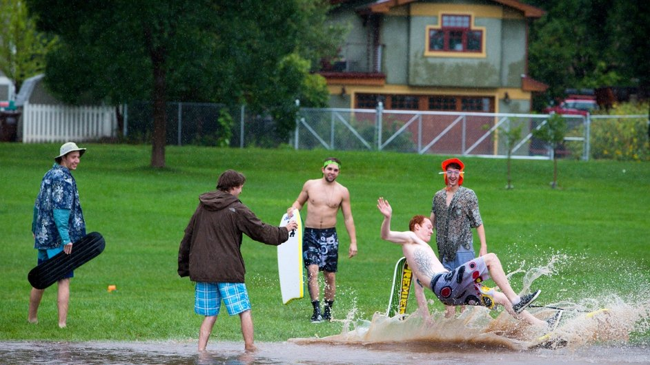 People play in flood waters after heavy rain in Boulder, Colorado