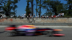 Crowds watch Red Bull's Sebastian Vettel from a wall during practice for the Italian Grand Prix at Monza