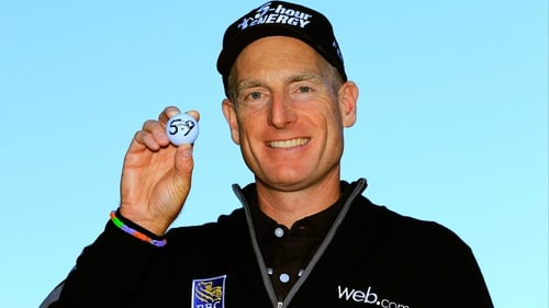 Jim Furyk holds up his ball with a '59' on it after shooting a 12 under round of 59