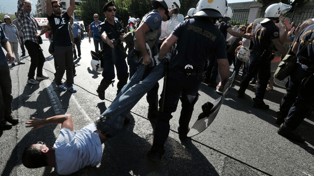 Greek policemen drag a protester as school guards demonstrate outside the Ministry of Administrative Reform