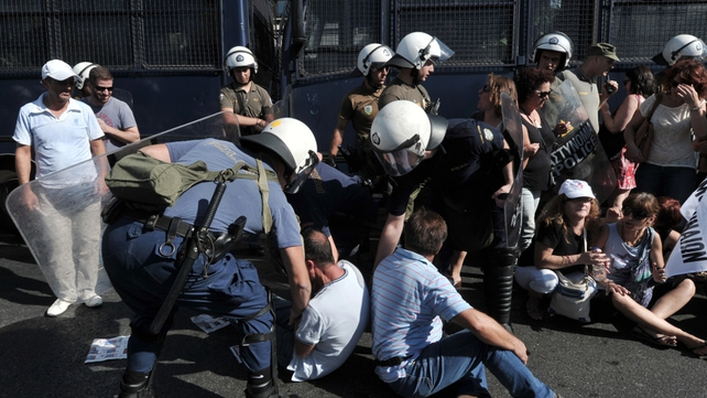 Police try to remove protesters from outside the Ministry
