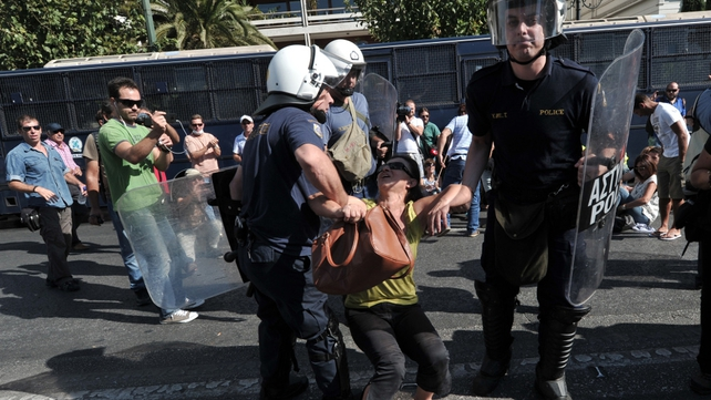 A woman is taken away by police during protests in Athens