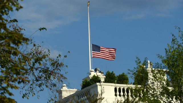 US flag flies at half-mast over the White House following the shootings