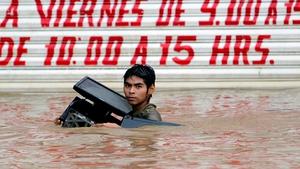 Residents waded neck-deep in brown muddy waters