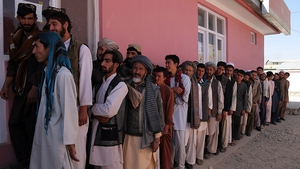 Afghan men wait to receive their identification cards to vote in upcoming elections at a registration centre in Ghazni