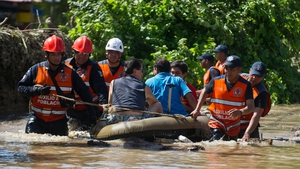 Rescued people are taken to safety by Mexican Federal Police officers on an inflatable dinghy in a flooded street of Acapulco