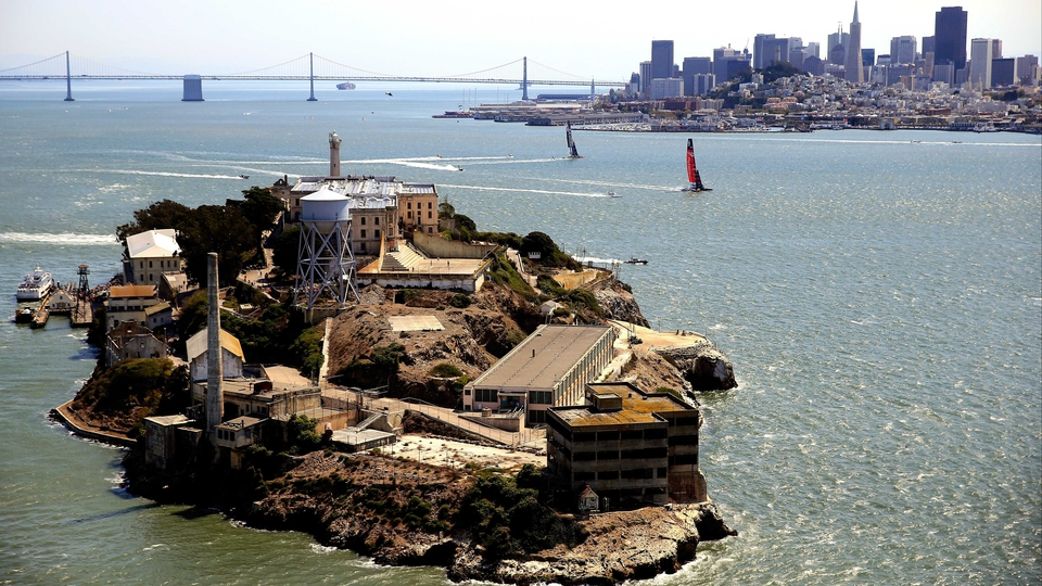 Oracle Team USA and Emirates Team New Zealand make their way towards Alcatraz Island in the America's Cup