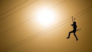 A photographer slides down a zip-line during the Rock in Rio Festival in Rio de Janeiro, Brazil