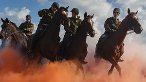 Dutch horsemen ride through coloured smoke during a practice session at the beach of Scheveningen